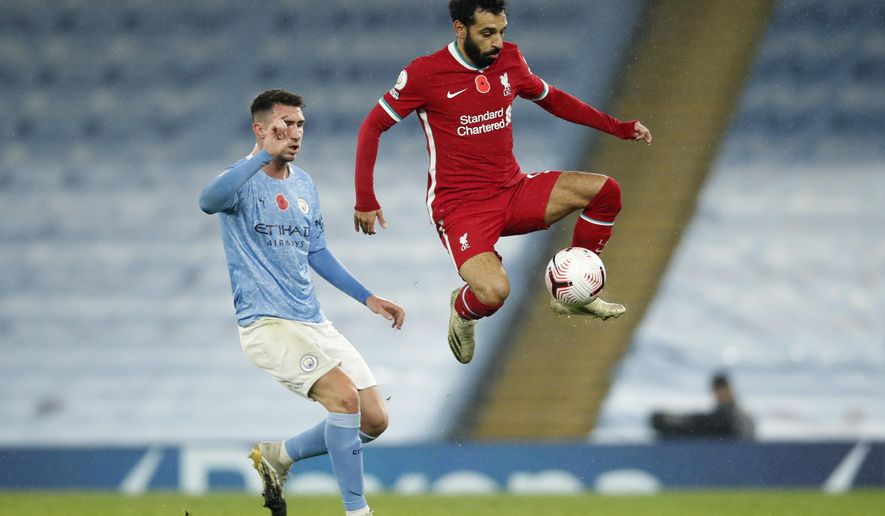 Liverpool's Mohamed Salah controls the ball next to Manchester City's Aymeric Laporte during the English Premier League soccer match between Manchester City and Liverpool at the Etihad stadium in Manchester, England, Sunday, Nov. 8, 2020. (Clive Brunskill/Pool via AP)