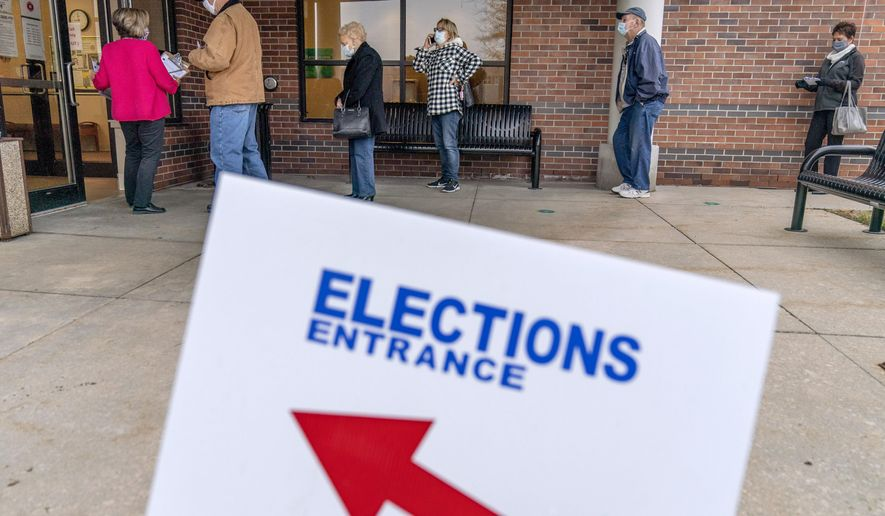 In this Oct. 29, 2020, file photo, voters line up as the doors open to the Election Center for absentee early voting for the general election in Sterling Heights, Mich. (AP Photo/David Goldman) ** FILE **