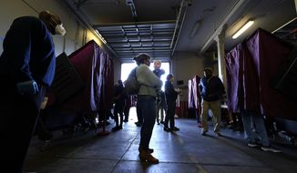 Amanda Bohren holds her one-year-old son, Luke Spencer Bohren, as she waits to vote on Election Day, in the Mid City section of New Orleans, Tuesday, Nov. 3, 2020. (AP Photo/Gerald Herbert)