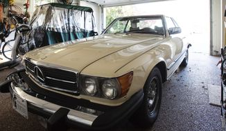 """Tom Jamieson's 1979 Mercedes-Benz 450 SL sits in a garage in Lansing, Mich. on Wednesday, Oct. 28, 2020. Jamieson who bought the car from Earvin """"Magic"""" Johnson in the 1980s, is now he's selling it, listing it for sale online for $24,000, according to the Lansing State Journal. (Matthew Dae Smith/Lansing State Journal via AP)"""