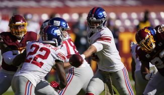 New York Giants quarterback Daniel Jones (8) hands the ball off to running back Wayne Gallman (22) during the first half of an NFL football game against the Washington Football Team, Sunday, Nov. 8, 2020, in Landover, Md. (AP Photo/Susan Walsh)