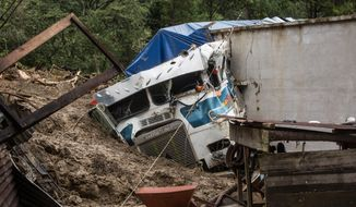 A semi is partially buried in a massive, rain-fueled landslide in the village of Queja, in Guatemala, Saturday, Nov. 7, 2020, in the aftermath of Tropical Storm Eta. (Esteban Biba/Pool Photo via AP)