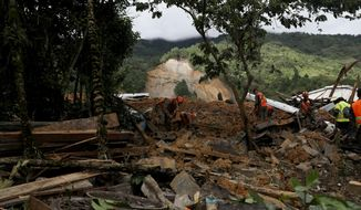 Members of search and recovery teams search for survivors in the debris of a massive, rain-fueled landslide in the village of Queja, in Guatemala, Saturday, Nov. 7, 2020, in the aftermath of Tropical Storm Eta. (Esteban Biba/Pool Photo via AP)