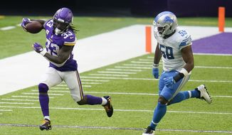 Minnesota Vikings running back Dalvin Cook (33) runs from Detroit Lions linebacker Reggie Ragland, right, during the second half of an NFL football game, Sunday, Nov. 8, 2020, in Minneapolis. (AP Photo/Jim Mone)