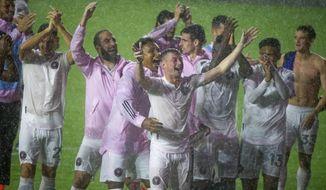 Inter Miami players greet fans in the rain after a win over FC Cincinnati in an MLS soccer match Sunday, Nov. 8, 2020, in Fort Lauderdale, Fla. (David Santiago/Miami Herald via AP)