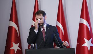 FILE - In this Friday, Aug. 10, 2018 file photo, Berat Albayrak, Turkey's Treasury and Finance Minister, wipes his forehead as he talks during a conference to ease investor concerns about Turkey's economic policy. Albayrak, announced his resignation on social media Sunday, Nov. 8, 2020. He said on Instagram that he was stepping down from his post for health reasons and would spend more time with his family. Albayrak, 42, was appointed minister of finance and treasury in July 2018, having previously been energy minister for nearly three years. (AP Photo/Mucahid Yapici, File)