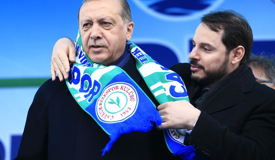 FILE - In this Monday, April 3, 2017 file photo, Berat Albayrak, right, Turkey's Energy Minister and son-in-law of Turkey's President Recep Tayyip Erdogan, left, places a soccer club scarf on his shoulders during a rally for the upcoming referendum, in his hometown city of Rize, in the Black Sea region, Turkey. Albayrak, announced his resignation on social media Sunday, Nov. 8, 2020. He said on Instagram that he was stepping down from his post for health reasons and would spend more time with his family.Albayrak, 42, was appointed minister of finance and treasury in July 2018, having previously been energy minister for nearly three years. (AP Photo/Lefteris Pitarakis, File)
