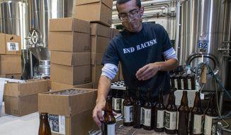 Jordan Vigil loads bottles in the brewery at Epic Brewing Co. in Salt Lake City, Thursday, Oct. 29, 2020. (Rick Egan/The Salt Lake Tribune via AP)