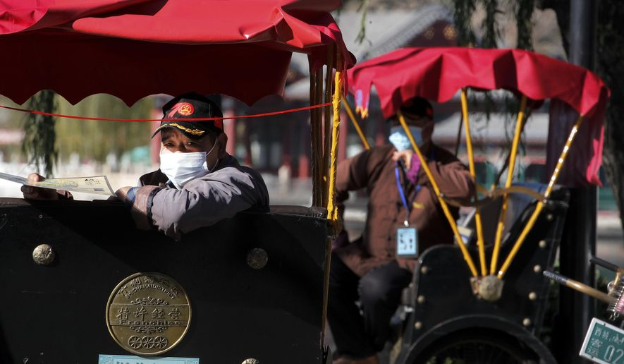 Trishaw drivers wearing face masks to help curb the spread of the coronavirus wait for customers near the Houhai Lake in Beijing, Sunday, Nov. 8, 2020. (AP Photo/Andy Wong)