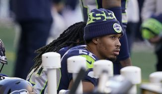 Seattle Seahawks cornerback Quinton Dunbar sits on the bench during the national anthem before an NFL football game against the San Francisco 49ers, Sunday, Nov. 1, 2020, in Seattle. (AP Photo/Elaine Thompson)