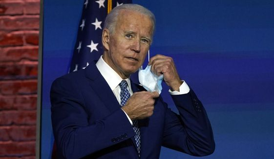 President-elect Joe Biden removes his face mask as he arrives to speak Monday, Nov. 9, 2020, at The Queen theater in Wilmington, Del. (AP Photo/Carolyn Kaster)