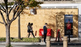 A Smoothie King on K Street in downtown Washington, is still boarded up, Monday, Nov. 9, 2020. While some storefronts downtown have begun to remove the boards protecting their windows since the election, many still remain. (AP Photo/Jacquelyn Martin)