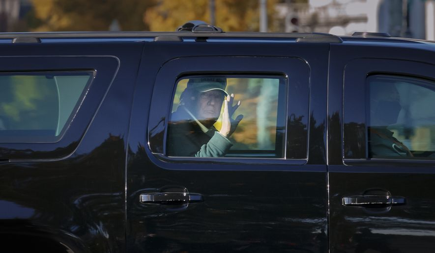 President Donald Trump waves to supporters as his motorcade arrives at the White House after golfing at his Trump National Golf Club in Sterling, Va., in Washington, Sunday, Nov. 8, 2020, a day after was defeated by President-elect Joe Biden. (AP Photo/J. Scott Applewhite)