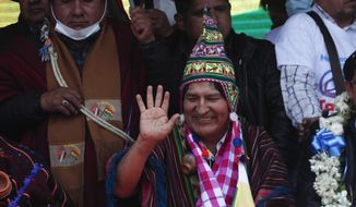 Former President Evo Morales waves during a rally with supporters in Villazon, Bolivia, Monday, Nov. 9, 2020, after he walked across a border bridge from Argentina. Morales, who fled into exile after resigning last November, returned to his homeland the day after the presidential inauguration of his former finance minister Luis Arce. (AP Photo/Juan Karita)
