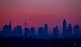 The buildings of the banking district are seen under a red sky before sunrise in Frankfurt, Germany, early Saturday, Nov. 7, 2020. (AP Photo/Michael Probst)