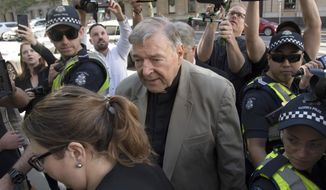 FILE - In this Feb. 27, 2019, file photo Cardinal George Pell arrives at the County Court in Melbourne, Australia. High-profile Australian journalists and large media organizations went on trial on Monday, Nov. 9, 2020, on charges that they breached a gag order on reporting about Cardinal George Pell's sex abuse convictions in 2018 that have since been overturned. (AP Photo/Andy Brownbill, File)