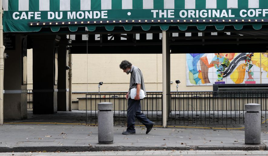 In this Friday, March 27, 2020, file photo, a man walks past the closed Cafe Du Monde restaurant in the French Quarter of New Orleans. (AP Photo/Gerald Herbert, File)