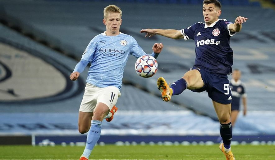 Olympiacos' Lazar Randelovic, right, duels for the ball with Manchester City's Oleksandr Zinchenko during the Champions League group C soccer match between Manchester City and Olympiacos at the Etihad stadium in Manchester, England, Tuesday, Nov. 3, 2020. (AP Photo/Dave Thompson)