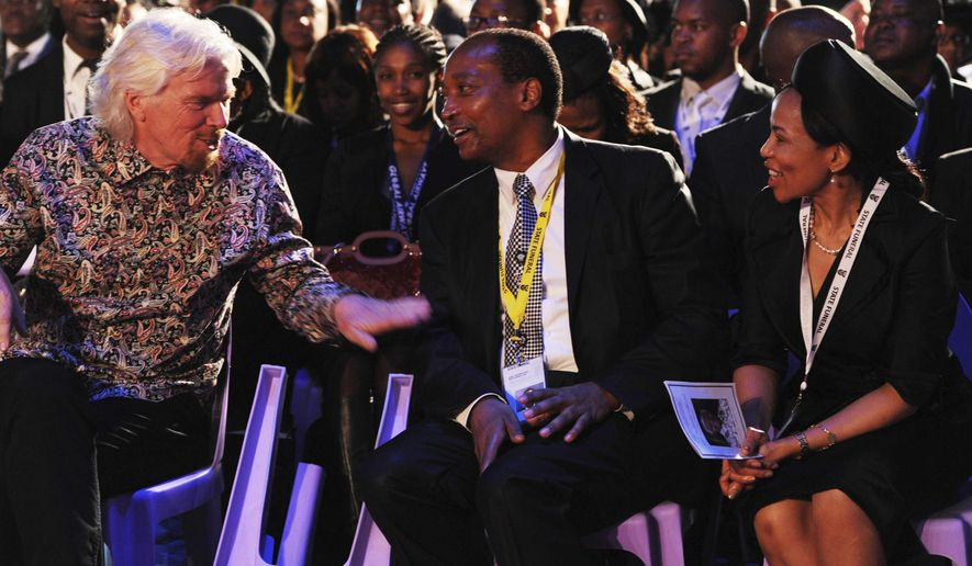 FILE - In this Dec. 15, 2013 file photo, British entrepreneur Richard Branson, left, speaks to South African billionaire Patrice Motsepe, centre, and his wife Precious Makgosi Moloi, right, before the funeral service for former South African President Nelson Mandela in Qunu, South Africa. South African businessman Patrice Motsepe entered the race to be president of the African soccer confederation on Monday Nov. 9, 2020. (AP Photo/Felix Dlangamandla, Pool, File)