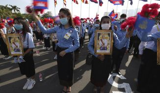 Cambodian students, holding the portrait of  King Norodom Sihamoni, participate in the country's 67th Independence Day celebration, in Phnom Penh, Cambodia, Monday, Nov. 9, 2020. (AP Photo/Heng Sinith)