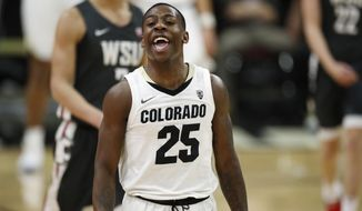FILE - Colorado guard McKinley Wright IV jokes with teammates as he heads to the bench late in the second half of an NCAA college basketball game against Washington State, in this Thursday, Jan. 23, 2020, file photo taken in Boulder, Colo. Wright, a Minnesota native, will return to play in his senior year at Colorado. (AP Photo/David Zalubowski, File)