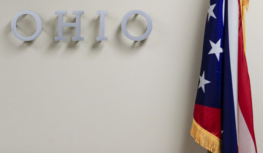 """The U.S. flag sits next to letters spelling """"Ohio"""" on a wall at the Hamilton County Board of Elections, Tuesday, Nov. 3, 2020, in Norwood, Ohio. (AP Photo/Aaron Doster)"""