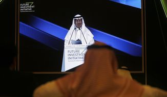 FILE - In this Oct. 30, 2019 file photo, participants watch Saudi Energy Minister Prince Abdulaziz bin Salman on a screen during his speech at the Future Investment Initiative Forum, in Riyadh, Saudi Arabia. The minister said Monday, Nov. 9, 2020, that global energy producers have the ability to tweak an agreement on production cuts that could be extended through the end of 2022, signaling the anticipation of continued weakened demand for crude as the coronavirus pandemic impacts consumption and grounds air travel for many. (AP Photo/Amr Nabil, File)
