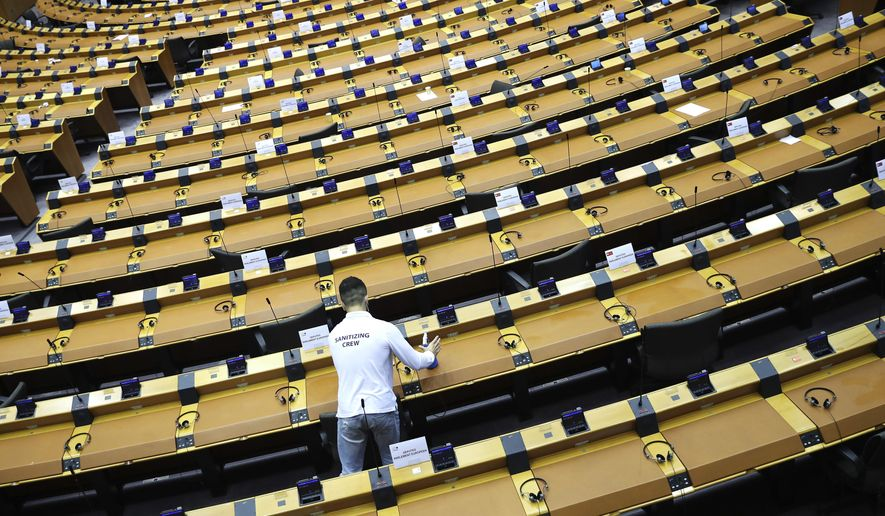 FILE - In this file photo dated Wednesday, Sept. 16, 2020, a member of the cleaning crew sanitizes desks at the European Parliament in Brussels.  EU lawmakers and the European Council reached a provisional political agreement on Monday Nov. 9, 2020, to update controls of so-called dual use goods such as facial recognition technology and spyware to prevent them from being used to violate human rights, although the agreement still needs formal approval from the EU Parliament.(AP Photo/Francisco Seco, FILE)