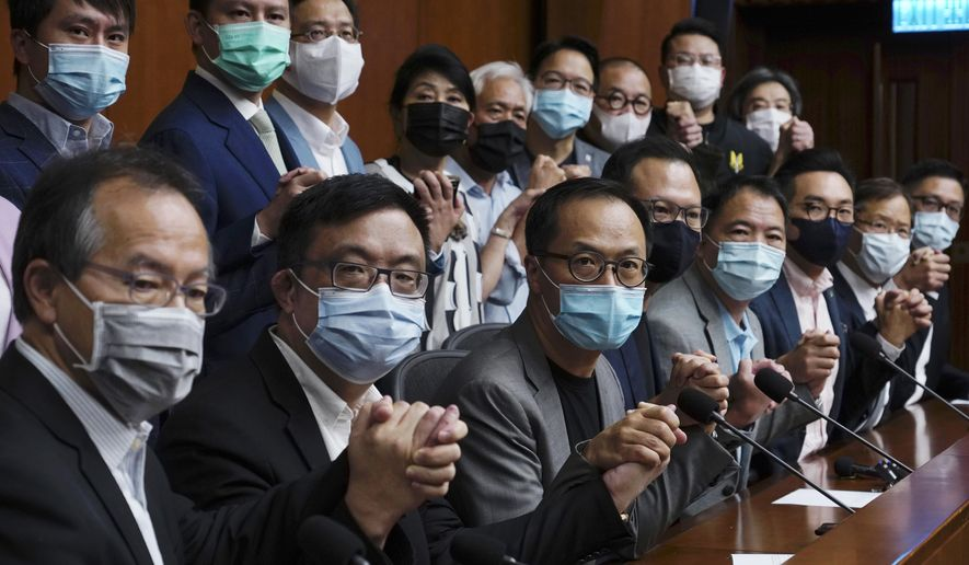 Hong Kong's pro-democracy legislators pose a picture before a press conference at the Legislative Council in Hong Kong, Monday, Nov. 9, 2020. The lawmakers said Monday that they would resign en masse if Beijing disqualifies any of them. The announcement came amid unconfirmed reports that Beijing would oust four legislators for filibustering meetings and violating their oath. (AP Photo/Vincent Yu)