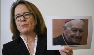 Anne Barrett Doyle, co-director of BishopAccountability.org, holds a photo of ex Cardinal Theodore McCarrick as she talks to the media during a press conference at the Foreign Press association headquarters, on the occasion of the first anniversary of Pope Francis' summit on clergy abuse, in Rome, Monday, Feb. 17, 2020. (AP Photo/Andrew Medichini)