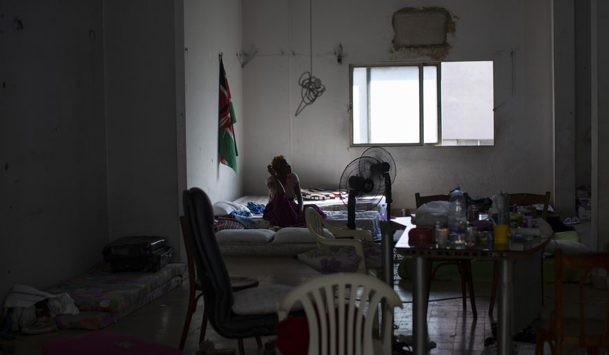 Natasha, a Kenyan migrant worker sits in a shelter where she is staying with other migrants, in Mkalles, Lebanon, Oct. 9, 2020. Two young Lebanese are on a mission to repatriate migrant workers who have been stranded in Lebanon amid the worst economic crisis in the country's modern history. In two months, they have sent more than 120 women, mostly Kenyans and some Ethiopians, back home, fundraising more than $35,000 for flights and coronavirus tests. (AP Photo/Hassan Ammar)