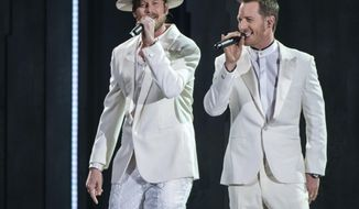 """FILE - Brian Kelley, left, and Tyler Hubbard of Florida Georgia Line perform """"Meant to Be"""" at the 52nd annual CMA Awards in Nashville, Tenn.  on Nov. 14, 2018. Hubbard is the second artist so far that will miss a scheduled performance at the CMA Awards on Wednesday due to COVID-19. He posted a note on his Instagram page on Monday, Nov. 9, 2020, saying he was asymptomatic and quarantining on his bus outside his home. It comes days after another artist, Lee Brice, also revealed he had tested positive and would not perform on the show.  (Photo by Charles Sykes/Invision/AP, File)"""
