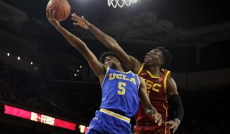 FILE - In this Saturday, March 7, 2020, file photo, UCLA guard Chris Smith (5) drives to the basket as Southern California forward Onyeka Okongwu defends during the second half of an NCAA college basketball game, in Los Angeles. After flirting with the NBA draft, Smith has returned to UCLA for the 2020-21 season. (AP Photo/Marcio Jose Sanchez, File)