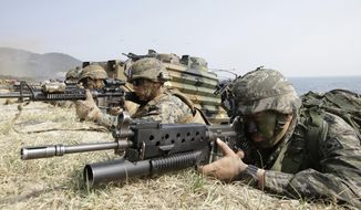 In this March 30, 2015, photo, marines of South Korea, right, and the U.S aim their weapons near amphibious assault vehicles during U.S.-South Korea joint landing military exercises as part of the annual joint military exercise Foal Eagle between the two countries in Pohang, South Korea. As Americans celebrate or fume over the new president-elect, many in Asia are waking up to the reality of a Joe Biden administration with decidedly mixed feelings. Relief and hopes of economic and environmental revival jostle with needling anxiety and fears of inattention. For South Korea, the new president will likely demonstrate more respect toward its treaty ally than Trump, who unilaterally downsized joint military training and constantly complained about the cost of the 28,500 U.S. troops stationed in the South to defend against North Korea.  (AP Photo/Lee Jin-man) **FILE**