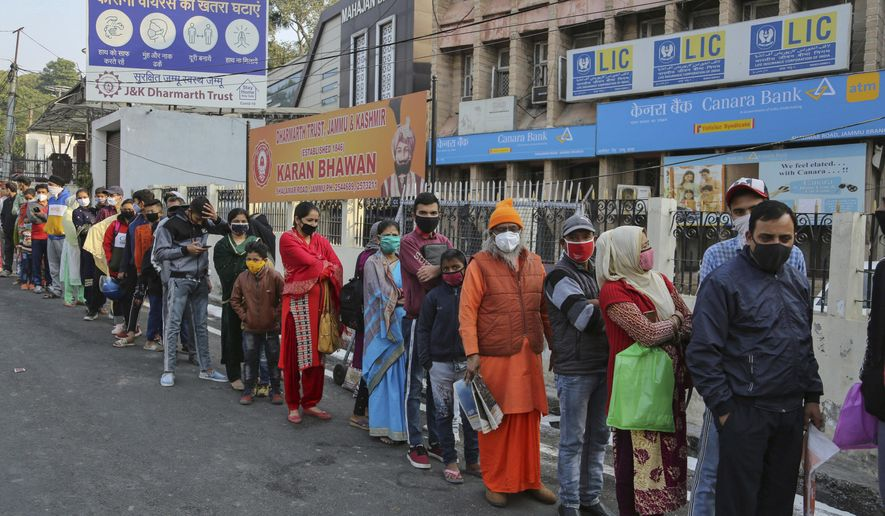 People wearing masks as a precaution against the coronavirus wait in a long queue to update details of their Aadhar, a government identity card in Jammu, India, Monday, Nov. 9, 2020. The updating services had temporally been suspended during the lockdown. (AP Photo/Channi Anand)