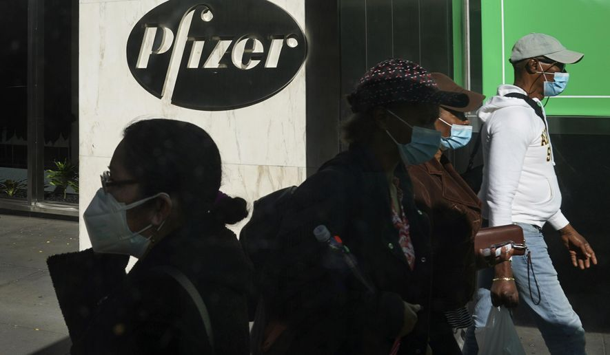 Pedestrians walk past Pfizer world headquarters in New York on Monday Nov. 9, 2020. Pfizer says an early peek at its vaccine data suggests the shots may be 90% effective at preventing COVID-19, but it doesn't mean a vaccine is imminent. (AP Photo/Bebeto Matthews)