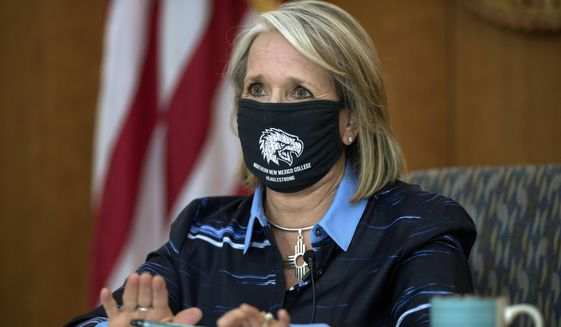 In this Thursday, July 23, 2020 file photo, Gov. Michelle Lujan Grisham gives her weekly update on COVID-19 and the state's effort to contain it during a virtual news conference from the state Capitol in Santa Fe, N.M. Grisham was an early adopter of aggressive pandemic restrictions that included a mask mandate, self-quarantine orders for travelers and a ban on public gatherings -- now capped at five people. And the state previously joined federal pilot project on testing and contact tracing. (Eddie Moore/The Albuquerque Journal via AP)