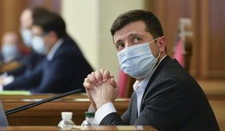 FILE - In this file photo dated Tuesday, March 31, 2020, Ukrainian President Volodymyr Zelenskiy wears a face mask to protect against coronavirus during an extraordinary parliamentary session in Kyiv, Ukraine.  It is announced Monday Nov. 9, 2020, that Volodymyr Zelenskiy has tested positive for the COVID-19 coronavirus.   (AP Photo, FILE)