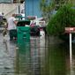 Residents clear debris from a flooded street in the aftermath of Tropical Storm Eta on Tuesday in Davie, Florida.