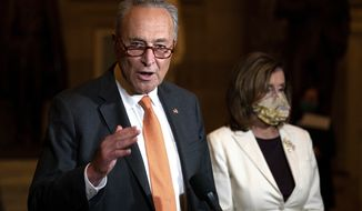 FILE - In this Aug. 6, 2020, file photo Senate Minority Leader Sen. Chuck Schumer of N.Y., speaks to reporters as House Speaker Nancy Pelosi of Calif., listens at right on Capitol Hill in Washington. On Tuesday, Nov. 10, Schumer, won his party's support to stay on leading the Democrats in the Senate, according to a Democrat granted anonymity to discuss the closed-door balloting. (AP Photo/Carolyn Kaster, File)