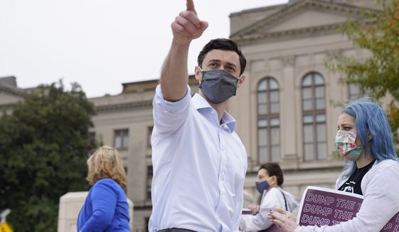 Democratic candidate for Senate Jon Ossoff points to a reporters after a news conference Tuesday, Nov. 10, 2020, in Atlanta. Ossoff is facing Republican Sen. David Perdue, a top Trump ally, in a Jan. 5, 2021 runoff.  (AP Photo/John Bazemore)
