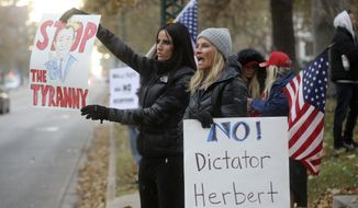 Stephanie Grant and Rebecca Olson protest Gov. Gary Herbert's mask mandate and new COVID-19 restrictions outside of the governor's mansion in Salt Lake City on Monday, Nov. 9, 2020. (Kristin Murphy/The Deseret News via AP)