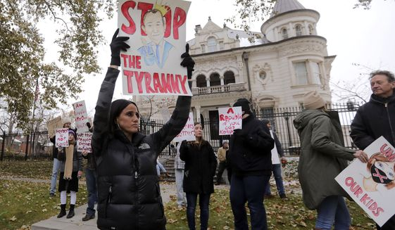 "Stephanie Grant holds a ""Stop the Tyranny"" sign during a protest of Gov. Gary Herbert's mask mandate and new COVID-19 restrictions outside of the Governor's Mansion in Salt Lake City on Monday, Nov. 9, 2020. (Kristin Murphy/The Deseret News via AP)"