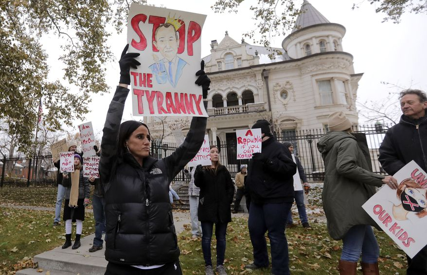 """Stephanie Grant holds a """"Stop the Tyranny"""" sign during a protest of Gov. Gary Herbert's mask mandate and new COVID-19 restrictions outside of the Governor's Mansion in Salt Lake City on Monday, Nov. 9, 2020. (Kristin Murphy/The Deseret News via AP)"""