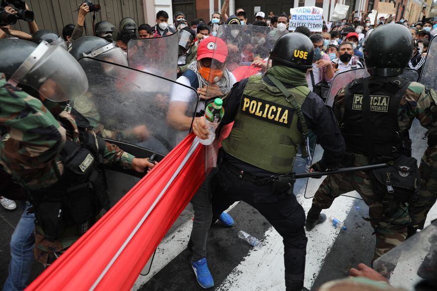 Police block supporters of former President Martin Vizcarra from reaching Congress as lawmakers swear-in Manuel Merino, head of Peru's legislature, as the new president in Lima, Peru, Tuesday, Nov. 10, 2020. Congress voted to oust Vizcarra over his handling of the new coronavirus pandemic and unproven allegations of corruption years ago. (AP Photo/Rodrigo Abd)