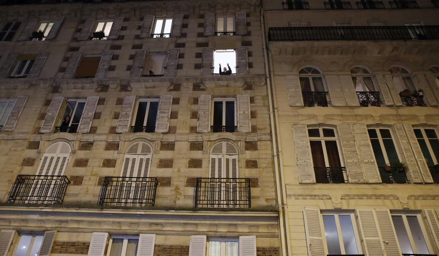 French tenor singer Stephane Senechal sings at dusk, the U.S. national anthem and Tosca of Puccini, from his apartment window during the monthlong partial lockdown to stop fast-rising virus hospitalizations and deaths, in Paris, Monday, Nov. 09, 2020. With more than 1.8 million infections since the start of the health crisis, France has Europe's highest cumulative total of recorded cases and the fourth-highest worldwide. (AP Photo/Francois Mori)