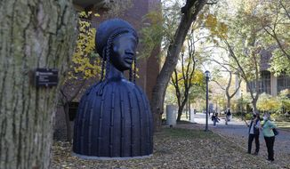 People look at a newly installed sculpture by artist Simone Leigh on the University campus in Philadelphia, Tuesday, Nov. 10, 2020. Leigh's 16-foot-tall bronze bust of a Black woman has been installed at the entrance to the heart of the University of Pennsylvania's campus. (AP Photo/Rebecca Blackwell)