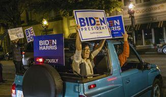 Supporters of President-elect Joe Biden and Vice President-elect Kamala Harris celebrate in Decatur, Ga., Saturday night, Nov. 7, 2020. (Jenni Girtman/Atlanta Journal-Constitution via AP)