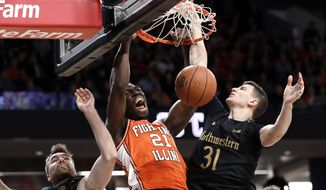 FILE - Illinois center Kofi Cockburn, center, reacts as he dunks against Northwestern guard Pat Spencer, left, and forward Robbie Beran during the first half of an NCAA college basketball game in Evanston, Ill., in this Thursday, Feb. 27, 2020, file photo. (AP Photo/Nam Y. Huh, File)