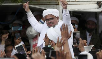 Indonesian Islamic cleric and the leader of Islamic Defenders Front Rizieq Shihab, center, gestures to his followers upon arrival from Saudi Arabia in Jakarta, Indonesia, Tuesday, Nov. 10, 2020. Thousands of followers of the firebrand cleric joyfully welcomed him at an the airport as he returned home from a 3-year exile in Saudi Arabia after criminal charges including a pornography case were dropped. (AP Photo/Achmad Ibrahim)